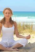 Woman doing yoga on the beach — Stock Photo