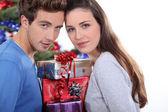 Jeune couple se tenait avec des tas de cadeaux — Photo