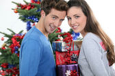 Excited young couple stood by the Christmas tree — Stock Photo