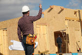 Tradesman standing in front of an unfinished house — Stock Photo