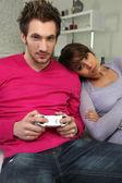 Woman watching boyfriend play video-games — Stock Photo