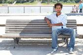молодой человек, сидя на скамейке в общественных — Стоковое фото