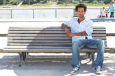 Young man sitting on a public bench — Stok fotoğraf