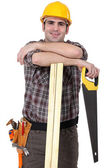 Carpenter with wood slats and saw — Stock Photo