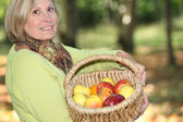 Woman carrying basket of apples — Stock Photo