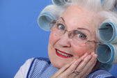 Elderly lady using hair rollers — Stock Photo