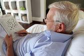 Grijs-haired mens voltooiing van kruiswoordraadsel — Stockfoto
