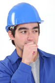 Closeup portrait of young craftsman looking amused with hand to his mouth — Stock Photo