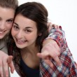 Two happy girls pointing at the camera — Stock Photo