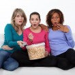 Three women eating popcorn whilst watching film - Zdjcie stockowe