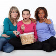 Three women eating popcorn whilst watching film - Photo