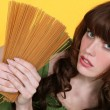 Woman holding uncooked spaghetti - Stock Photo