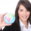 Woman holding out world globe — Stock Photo #11030981