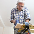 Grey-haired DIY fan drilling hole in wood — Stock Photo