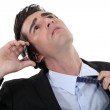 Businessman talking on the phone and taking off his tie — Stock Photo