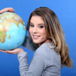 Attractive young woman holding a globe — Stock Photo