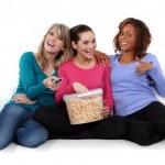 Three girls eating popcorn — Stock Photo