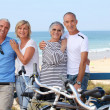 Portrait of four at the beach with bikes — Stock Photo