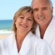 Couple at the beach in bathrobes — Stock Photo