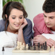 Young couple playing chess — Stock Photo