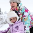 Mother and daughter playing in the snow — Stock Photo