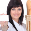 Woman baker showing businesscard — Stock Photo