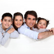 Family leaning on blank message board — Stock Photo