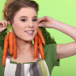 Funny woman holding carrots to her ears — Stock Photo #11034380