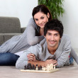 Couple sat at home playing chess — Stok fotoğraf