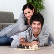 Couple sat at home playing chess — Stockfoto