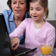 Young child looking at a laptop with her grandmother — Stock Photo