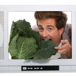 Man eating a cabbage inside a television — Stock Photo #11035938
