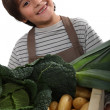 Child standing behind vegetables - Stockfoto