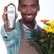 Florist smiling and holding a phone — Stok fotoğraf