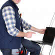 Royalty-Free Stock Photo: Handyman with laptop, studio shot