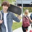 Student on campus with a skateboard — Stock Photo #11038107