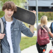 Student on campus with a skateboard - Stock Photo