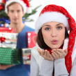 Woman with Christmas hat blowing kiss — Stock Photo