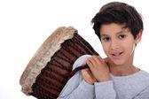 Little boy carrying bongo over shoulder — Stock Photo