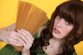 Woman holding uncooked spaghetti — Stock Photo
