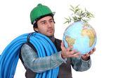 Plumber holding globe — Stock Photo