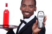 Restaurant waiter holding telephone — Stock Photo