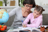 Mother teaching daughter from home — Stock Photo