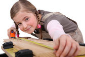 A child girl measuring a plank — Stock Photo