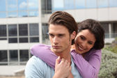 Couple embracing in front of building — Stock Photo