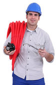 Plumber holding an economy filter faucet and a pig bank — Stock Photo