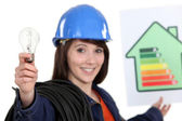Woman holding energy rating poster and light bulb — Stock Photo
