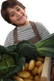 Child standing behind vegetables — Stock Photo
