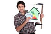 Hombre que tiene una etiqueta de consumo de energía y un montón de dinero en efectivo — Foto de Stock