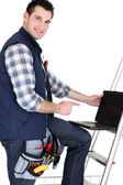 Handyman with laptop, studio shot — Stock Photo